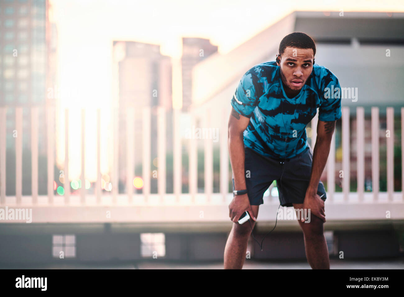 Young male runner taking a break on city roof in morning - Stock Image
