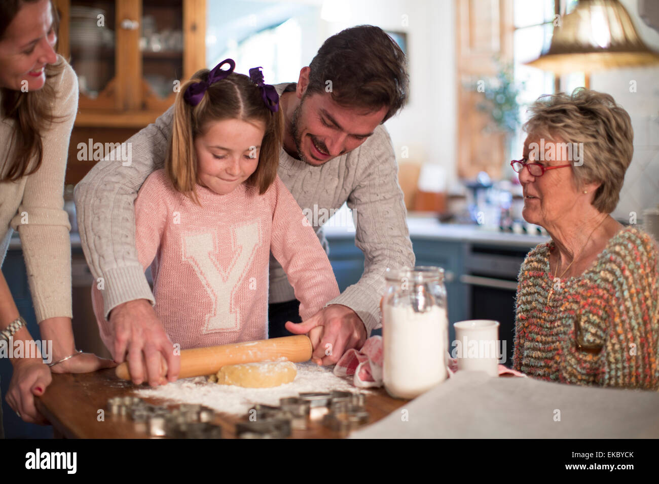Father and daughter rolling dough to make homemade cookies - Stock Image