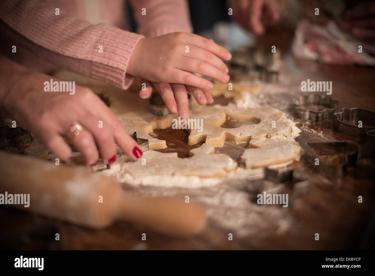Cutting shapes in dough to make homemade cookies - Stock Image