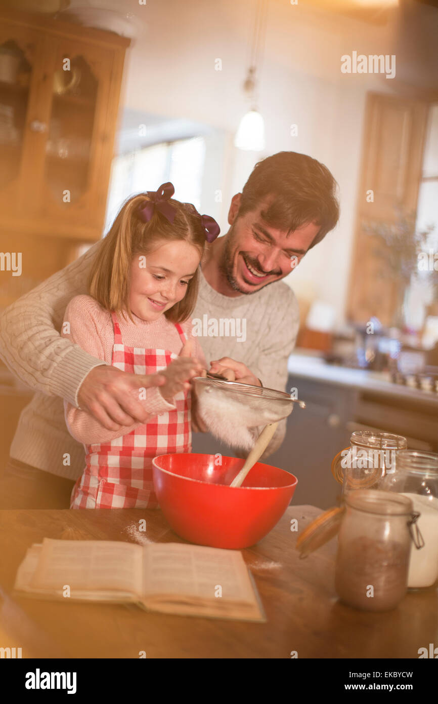 Father and daughter sifting flour into mixing bowl Stock Photo
