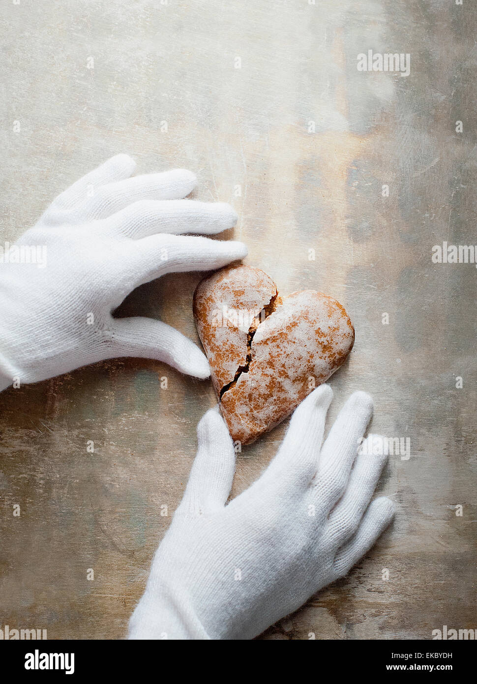 Gloved hands holding heart-shaped gingerbread cookie Stock Photo