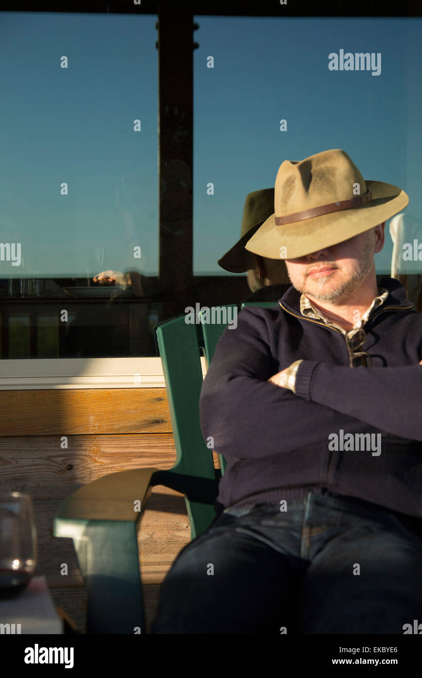 Man snoozing on chair with hat over eyes - Stock Image