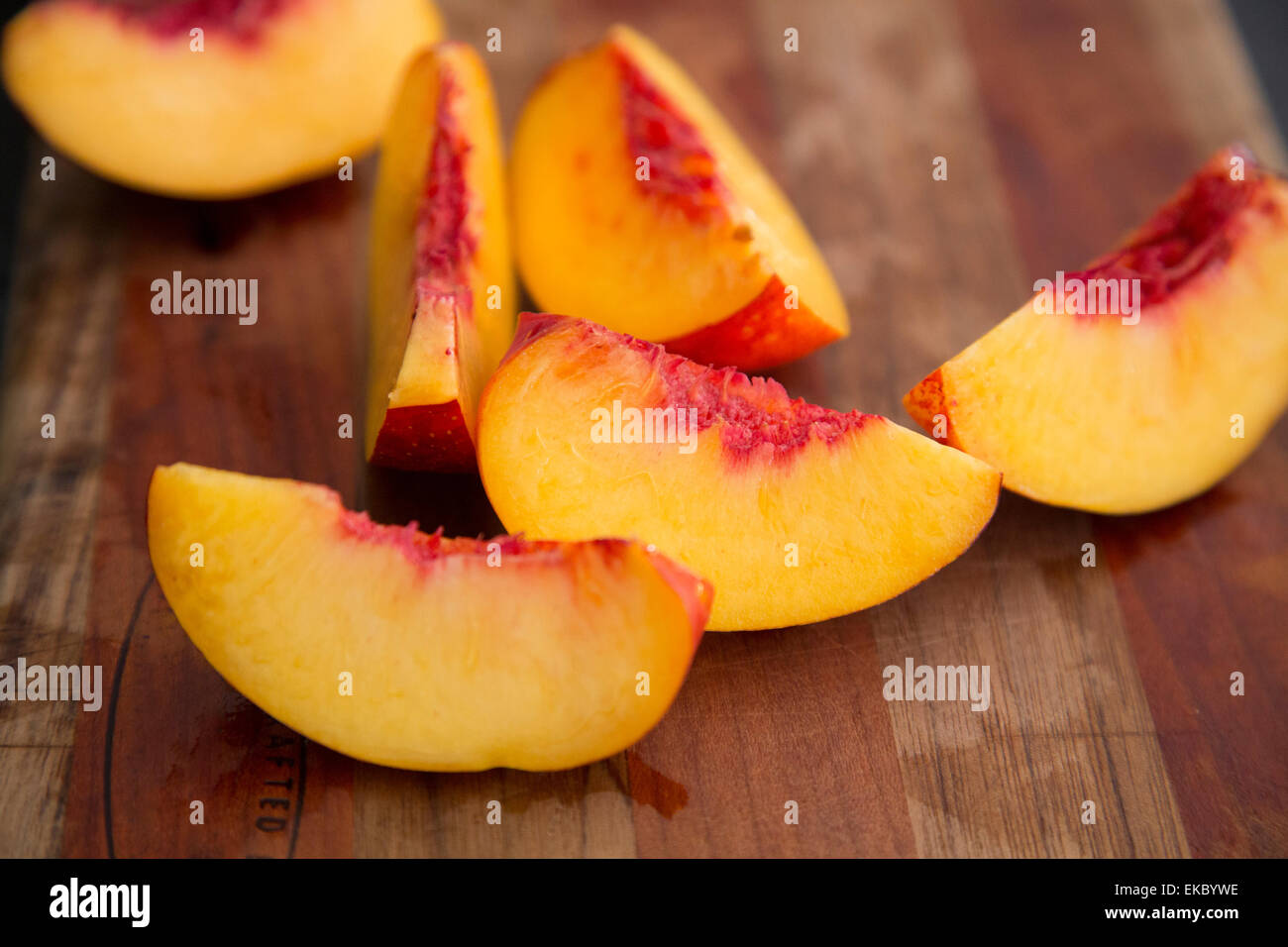 Peach slices on cutting board - Stock Image