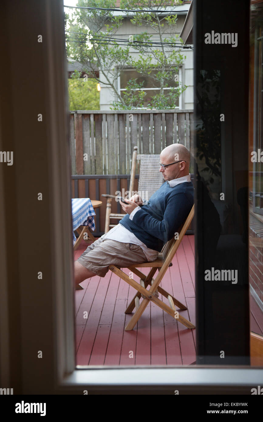 Man using phone on patio - Stock Image