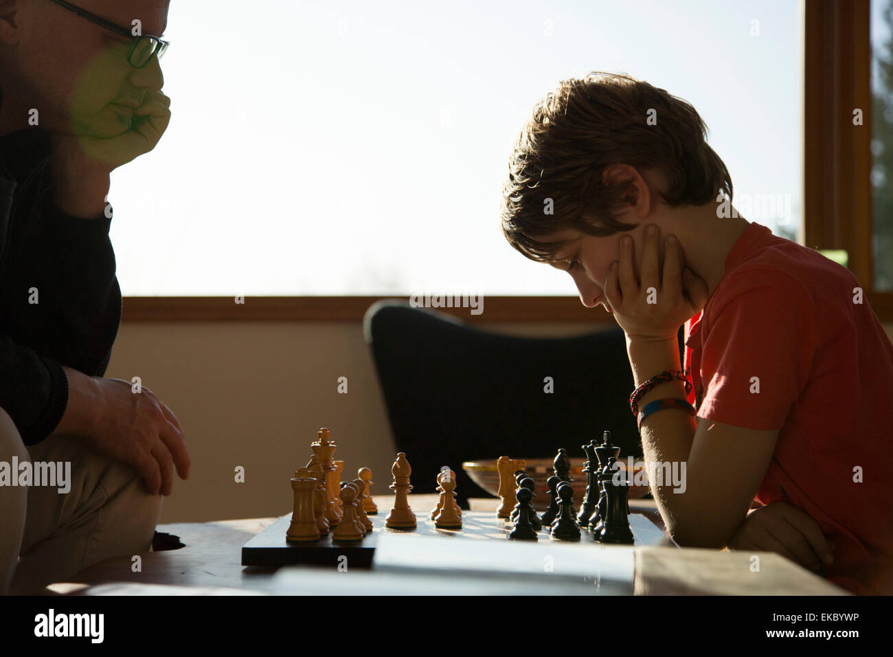 Father and son playing game of chess - Stock Image