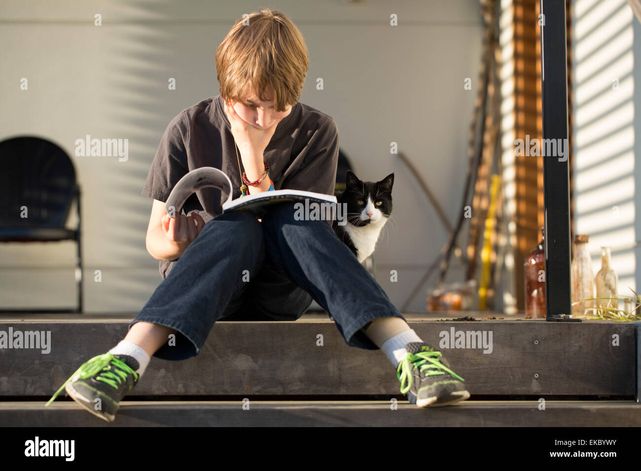Boy sitting on step reading book, cat peering from behind - Stock Image