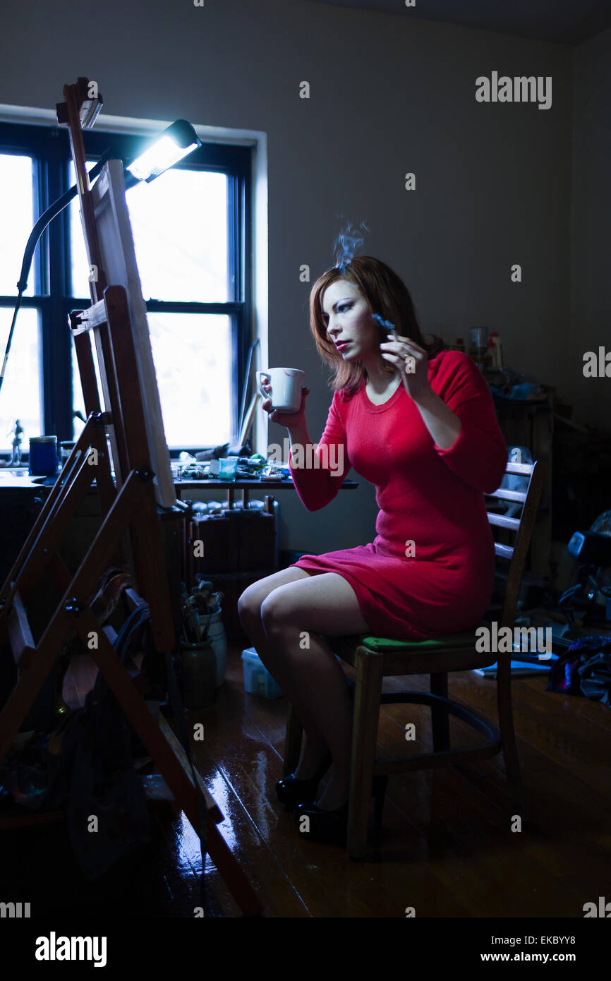 Mid adult woman sitting in front of easel, holding cigarette and hot drink - Stock Image
