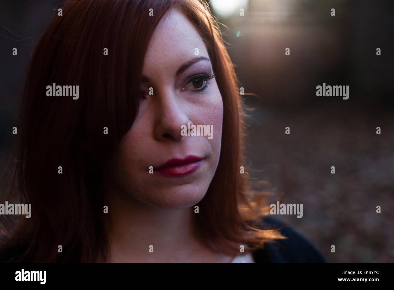 Portrait of mid adult woman, looking away, outdoors - Stock Image