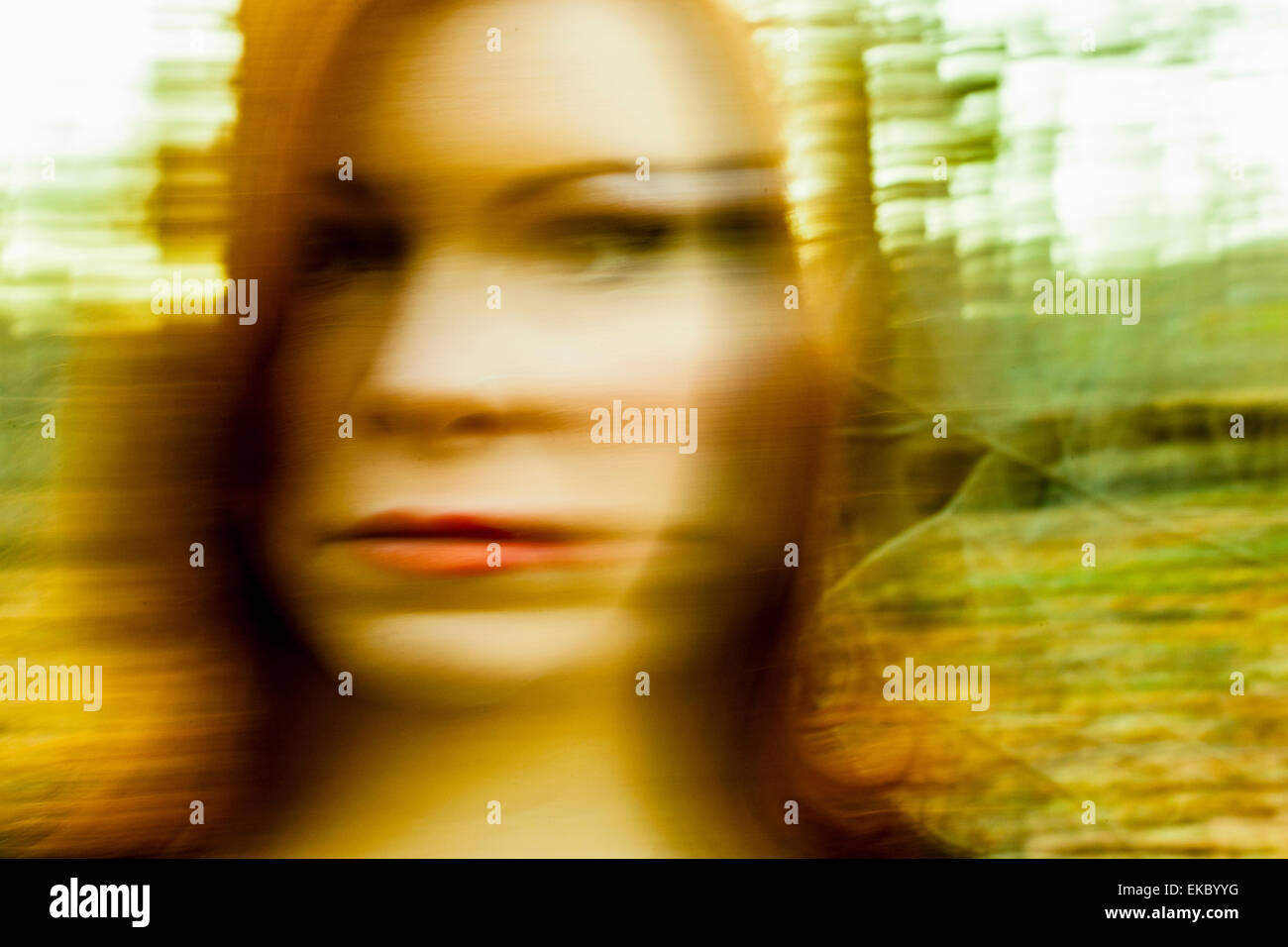 Portrait of mid adult woman, outdoors, blurred motion - Stock Image