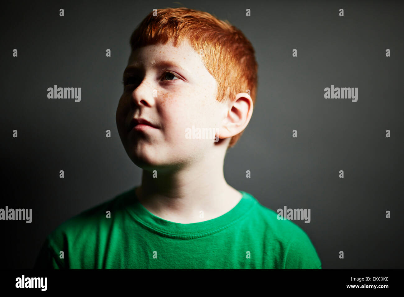Boy with red hair looking away - Stock Image