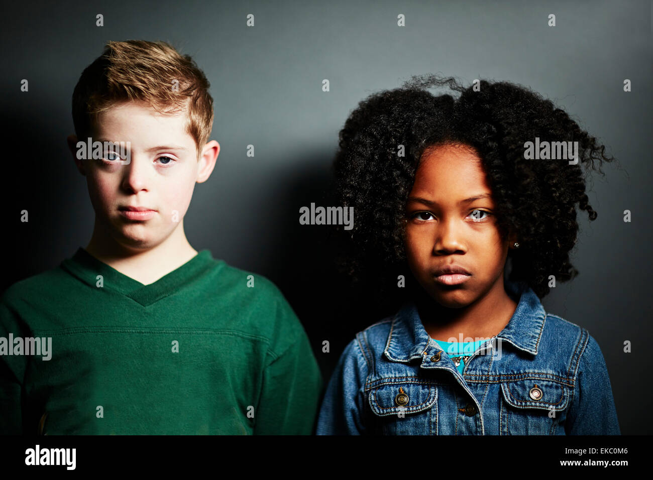 Portrait of a boy and girl looking serious - Stock Image