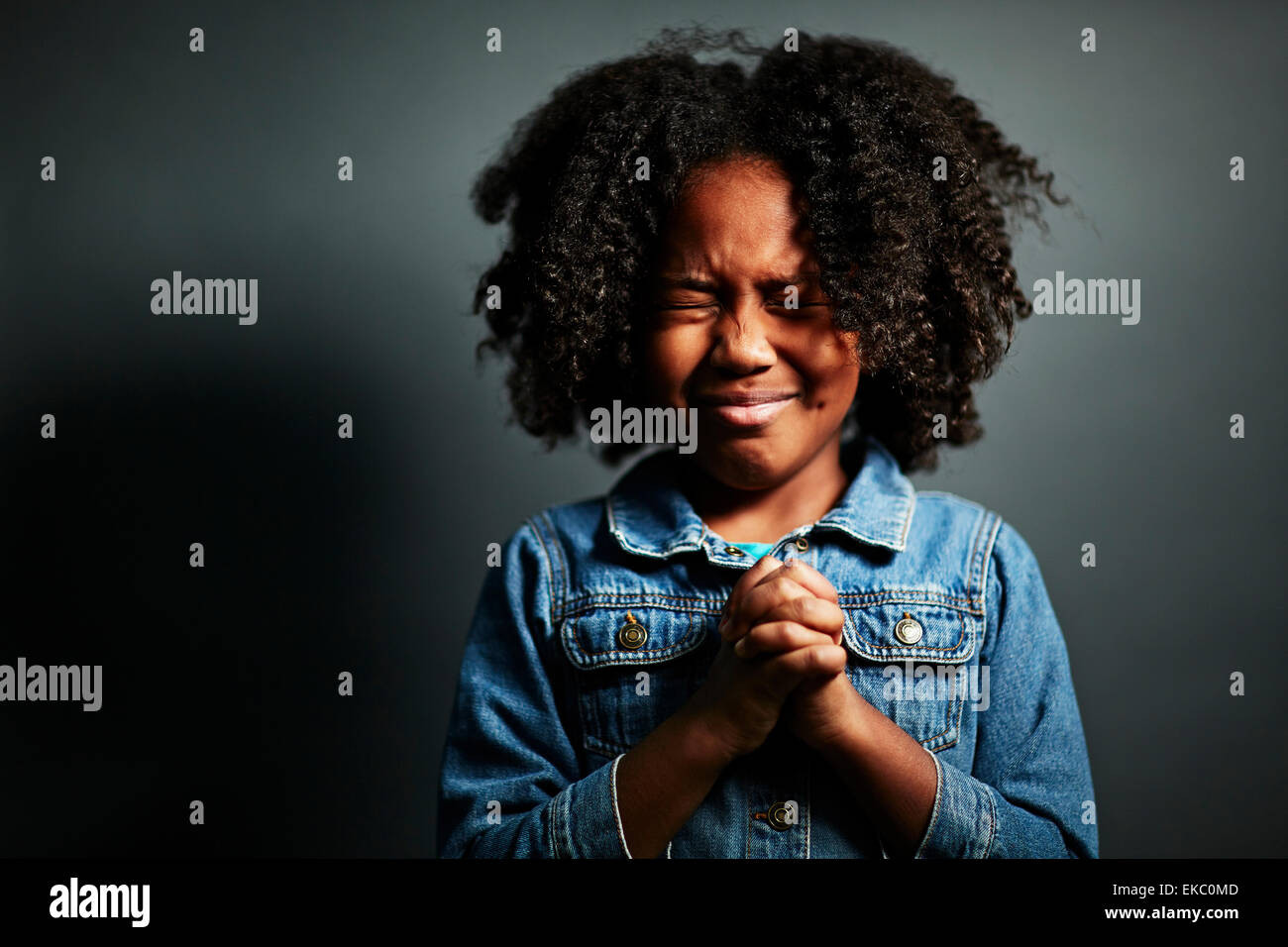 Girl with afro with hands clasped - Stock Image