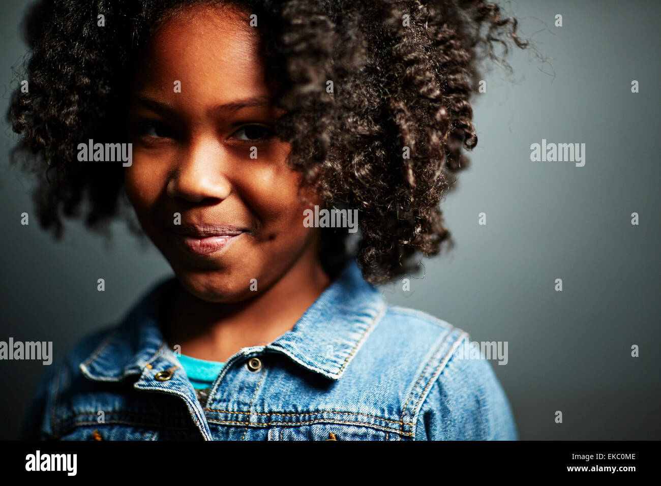 Girl with afro, smiling - Stock Image