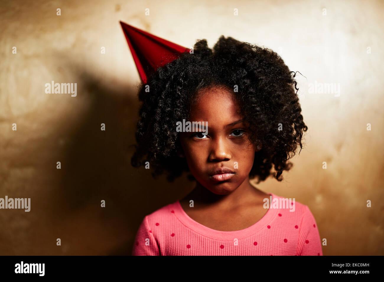 Sad girl wearing party hat - Stock Image
