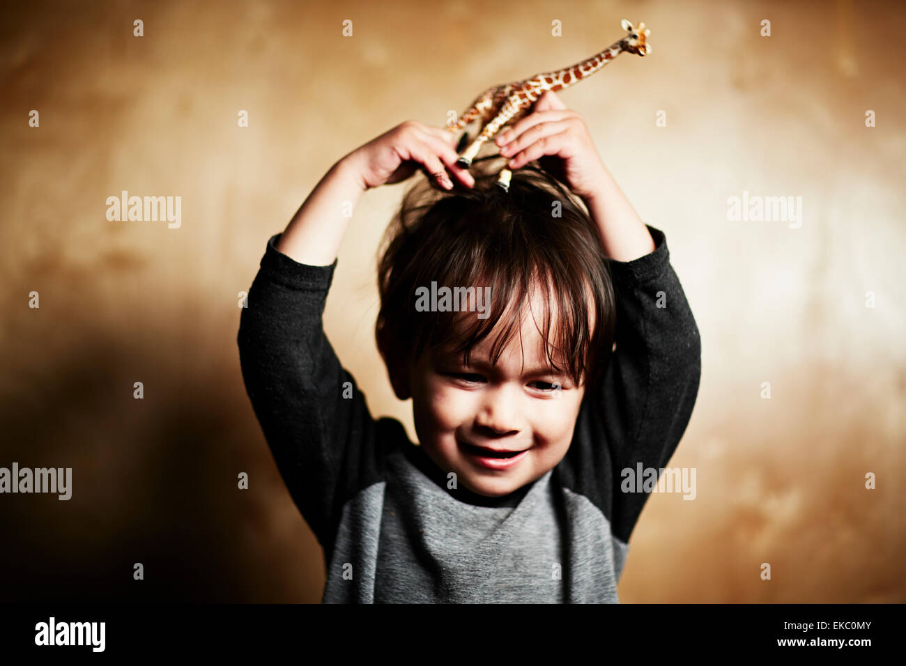 Portrait of cute male toddler holding toy giraffe on his head - Stock Image