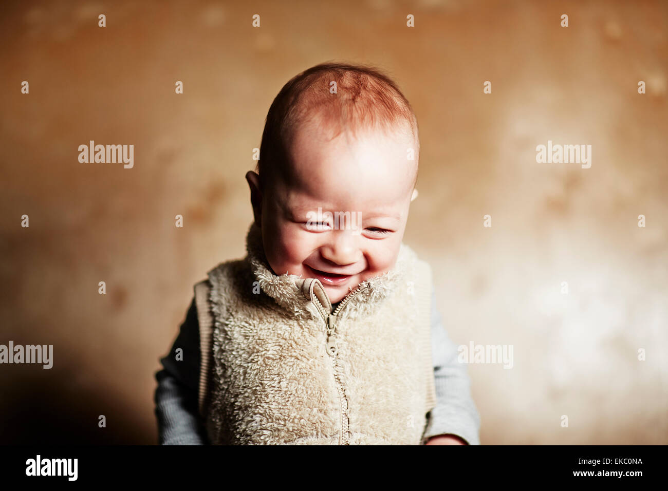 Portrait of cute baby boy looking down and giggling - Stock Image
