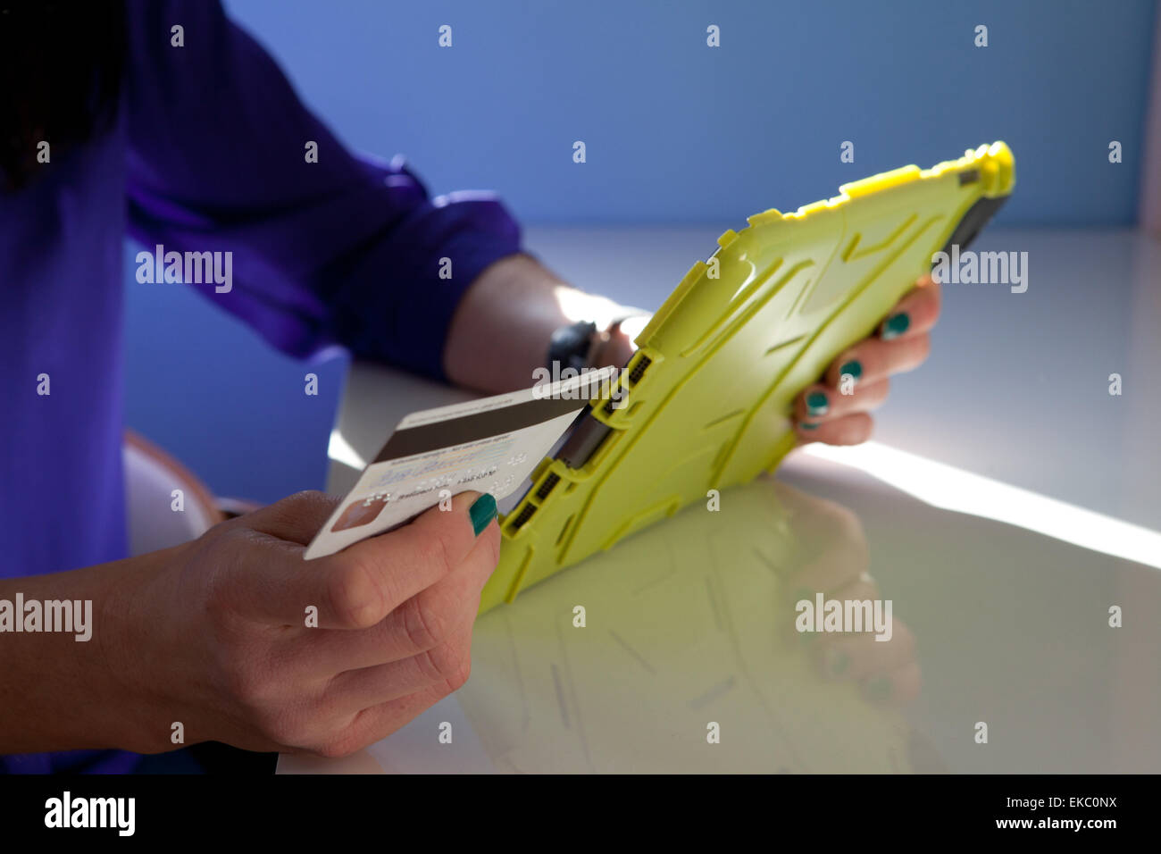 Cropped shot of woman making payment using credit card and digital tablet - Stock Image