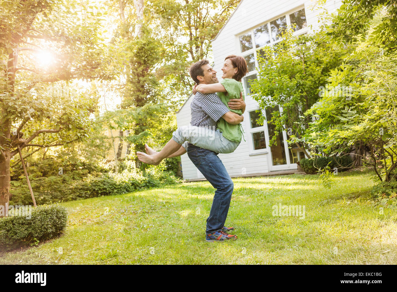 Couple hugging and playing in garden - Stock Image