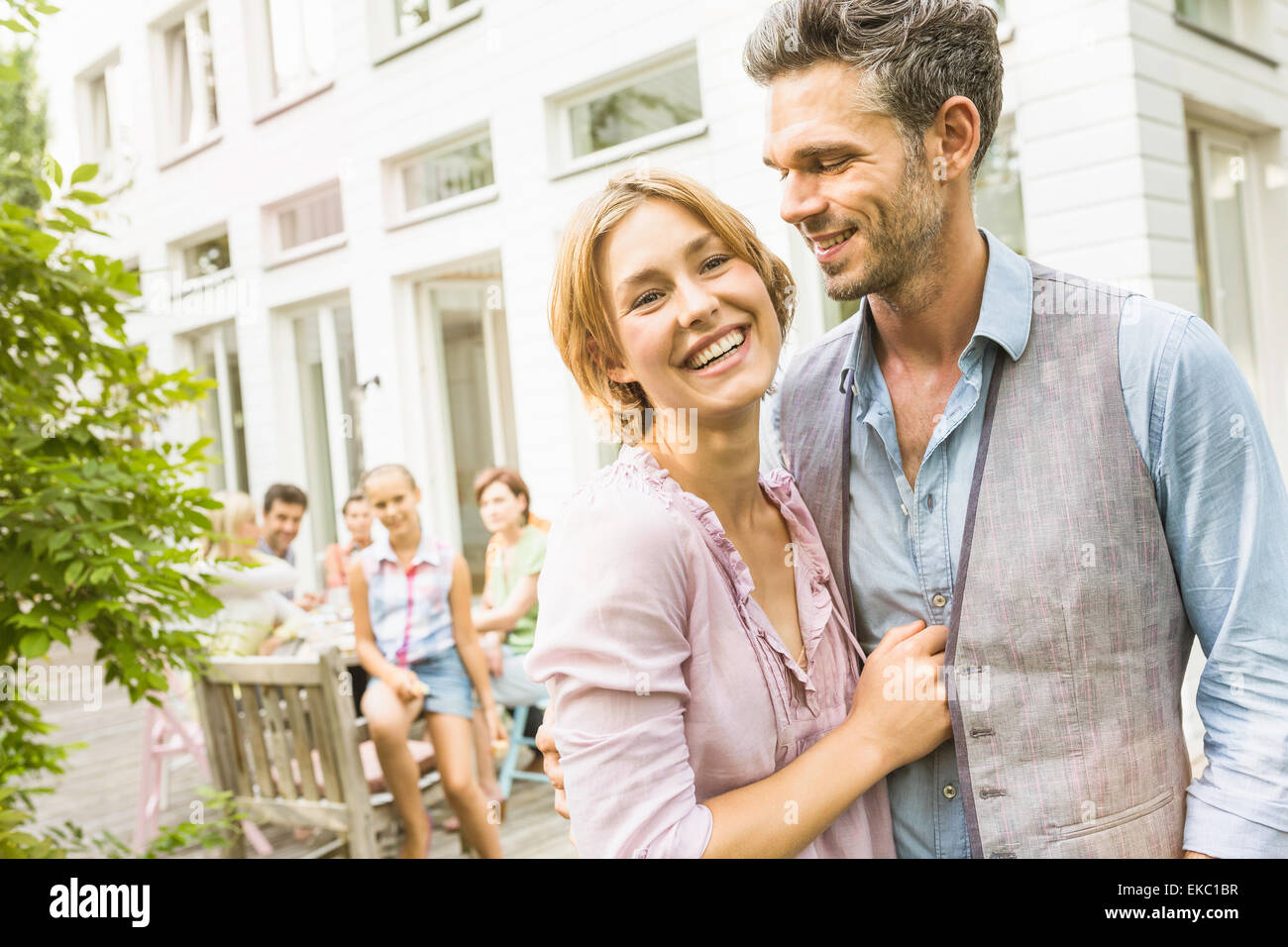Couple hugging in garden, family in background Stock Photo