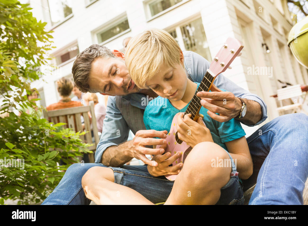 Father teaching son play ukulele in garden, family in background - Stock Image