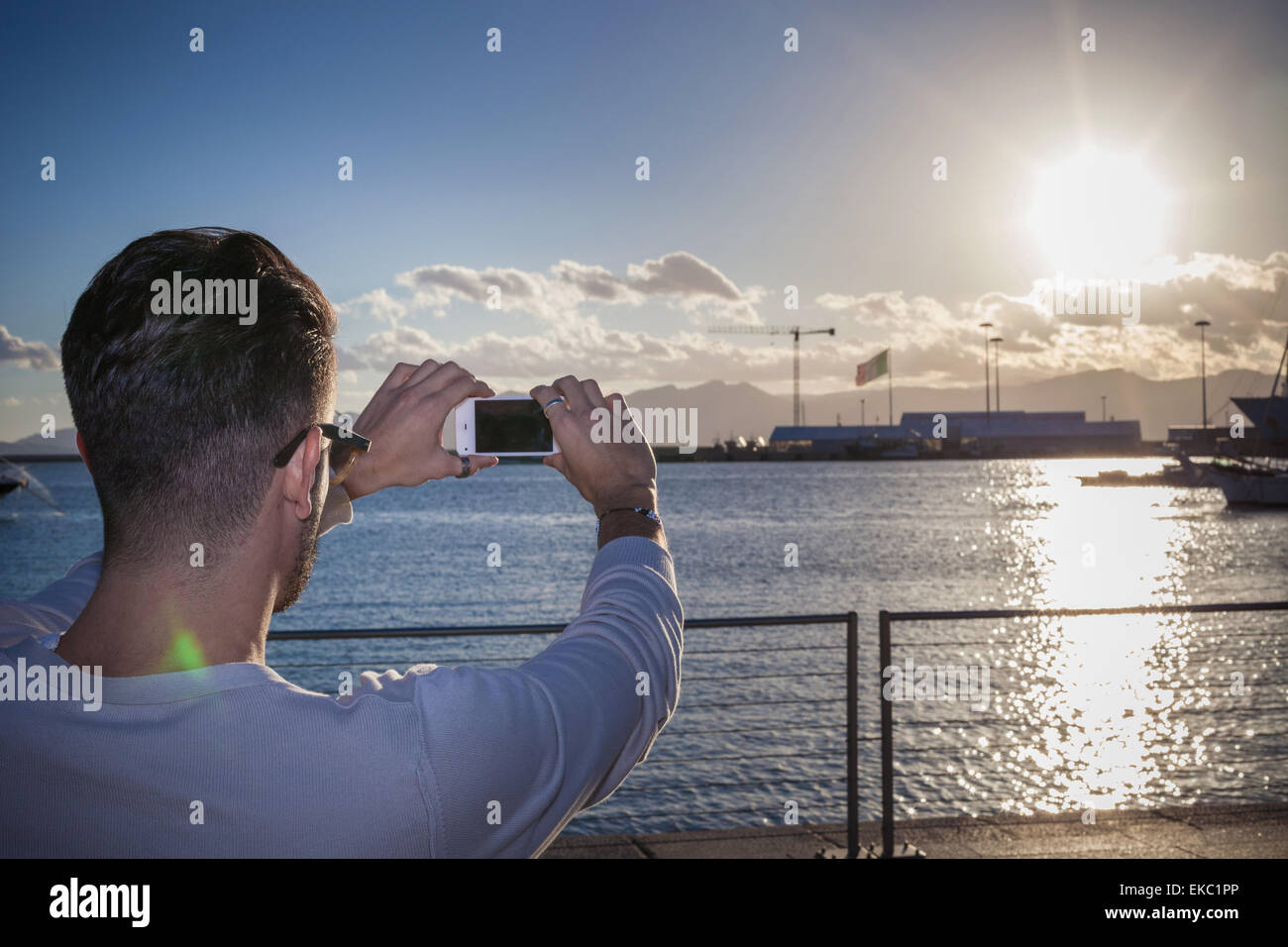Young man taking photograph of sunset by port, Cagliari, Sardinia, Italy - Stock Image