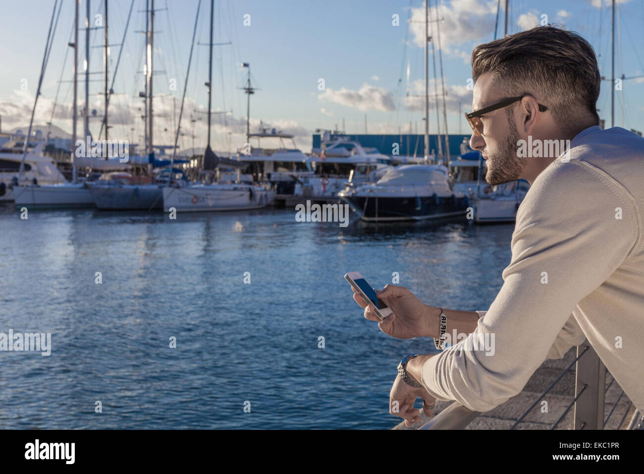 Young man using smartphone by port, Cagliari, Sardinia, Italy - Stock Image