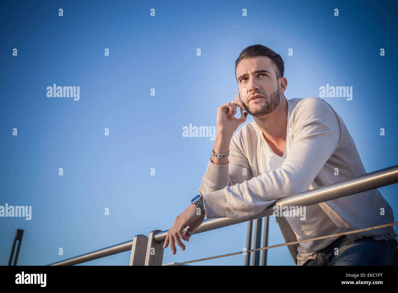 Young man using smartphone by port - Stock Image