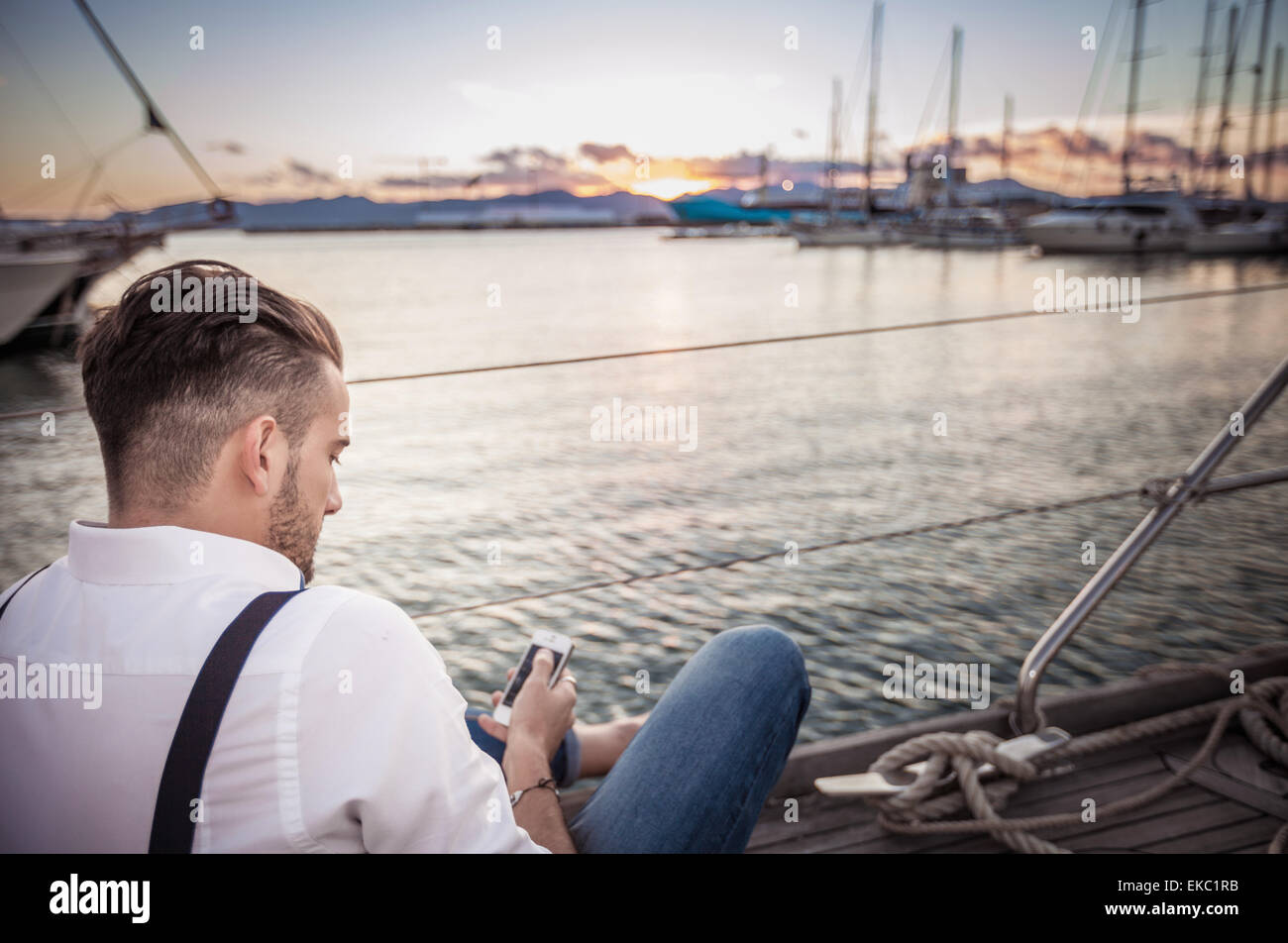 Young man using smartphone on yacht, Cagliari, Sardinia, Italy - Stock Image
