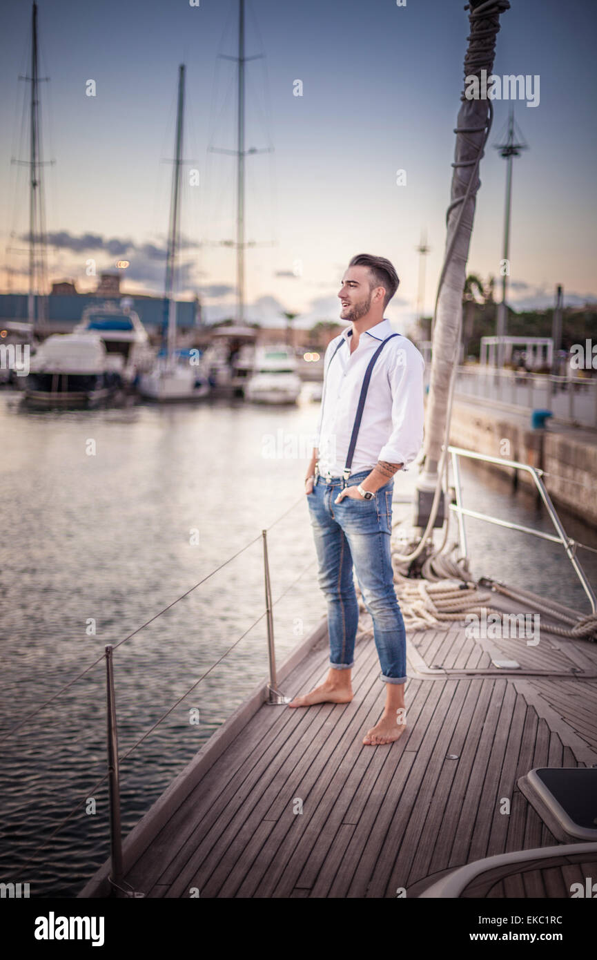 Young man relaxing on yacht, Cagliari, Sardinia, Italy - Stock Image