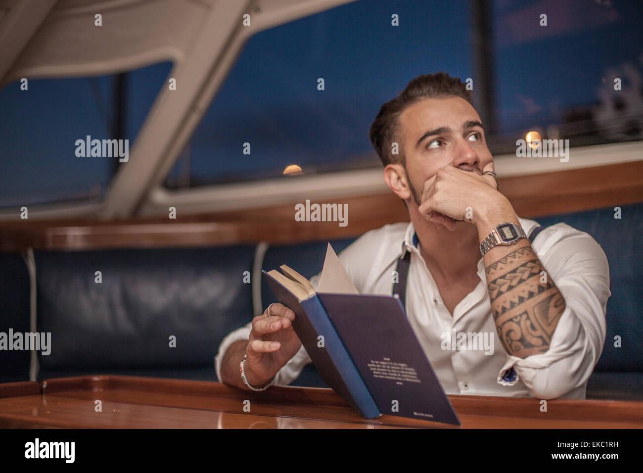 Young man reading inside yacht, Cagliari, Sardinia, Italy - Stock Image