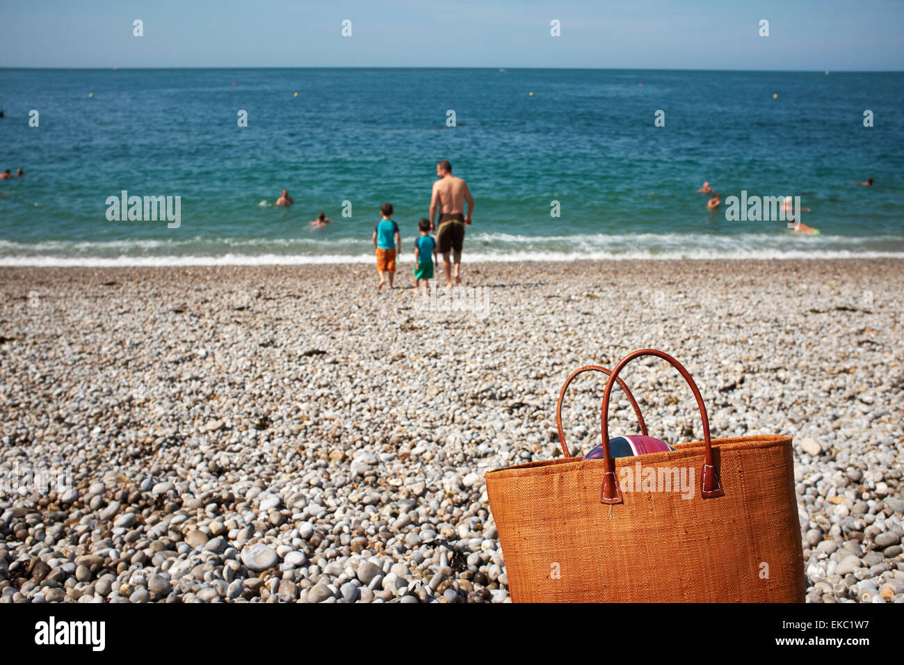 Rear view of father and two sons on beach, Normandy, France - Stock Image