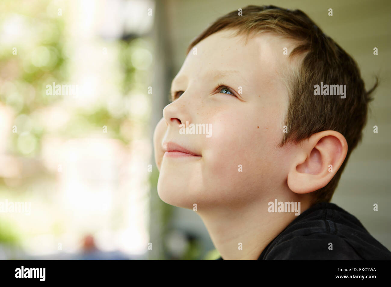 Close up profile portrait of boy in forest - Stock Image