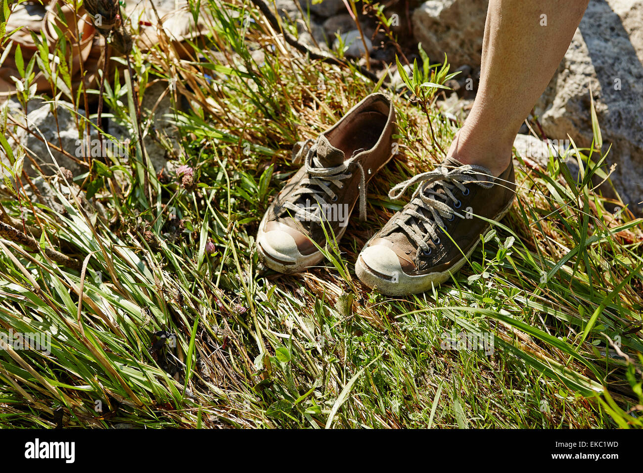 Cropped view of woman standing on one leg wearing trainers - Stock Image