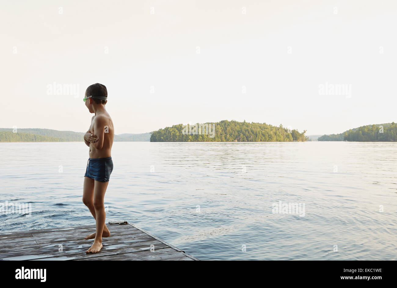 Boy looking out at lake from wooden pier, Ontario, Canada - Stock Image