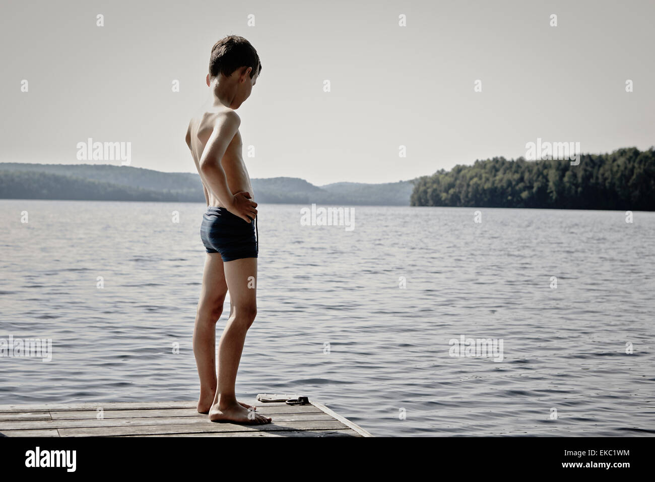 Boy looking down lake from wooden pier, Ontario, Canada - Stock Image