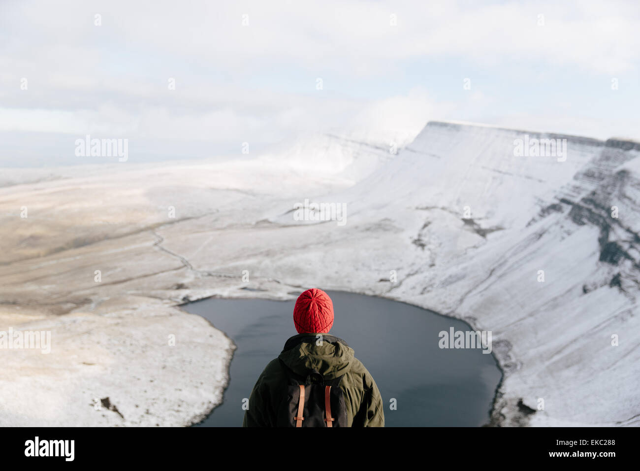 Rear view of man looking at Llyn y Fan Fach, The Brecon Beacons, Wales, UK - Stock Image