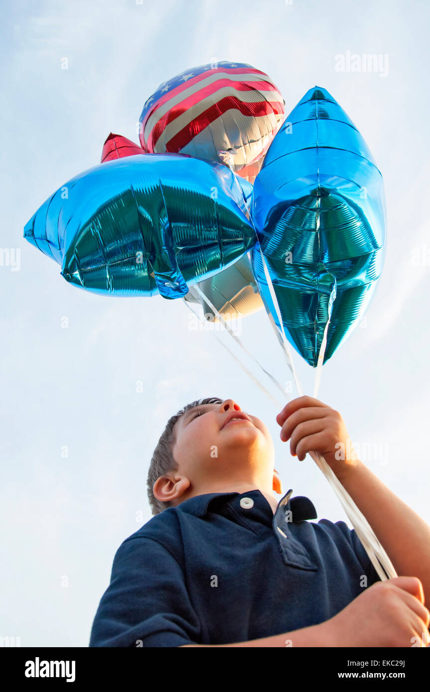 boy holding balloons - Stock Image
