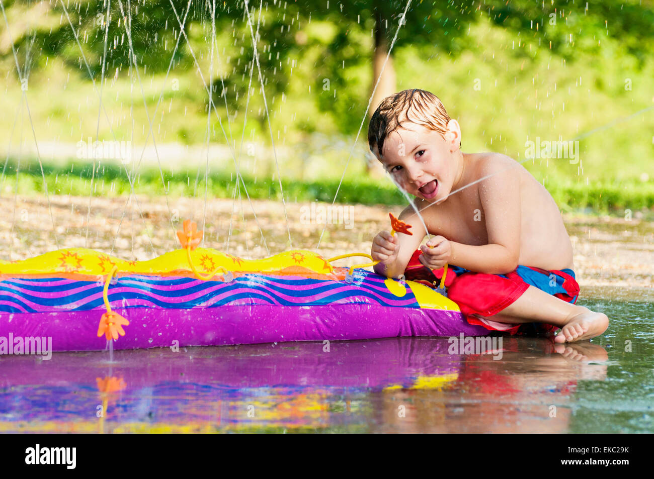 Young boy sprays water - Stock Image