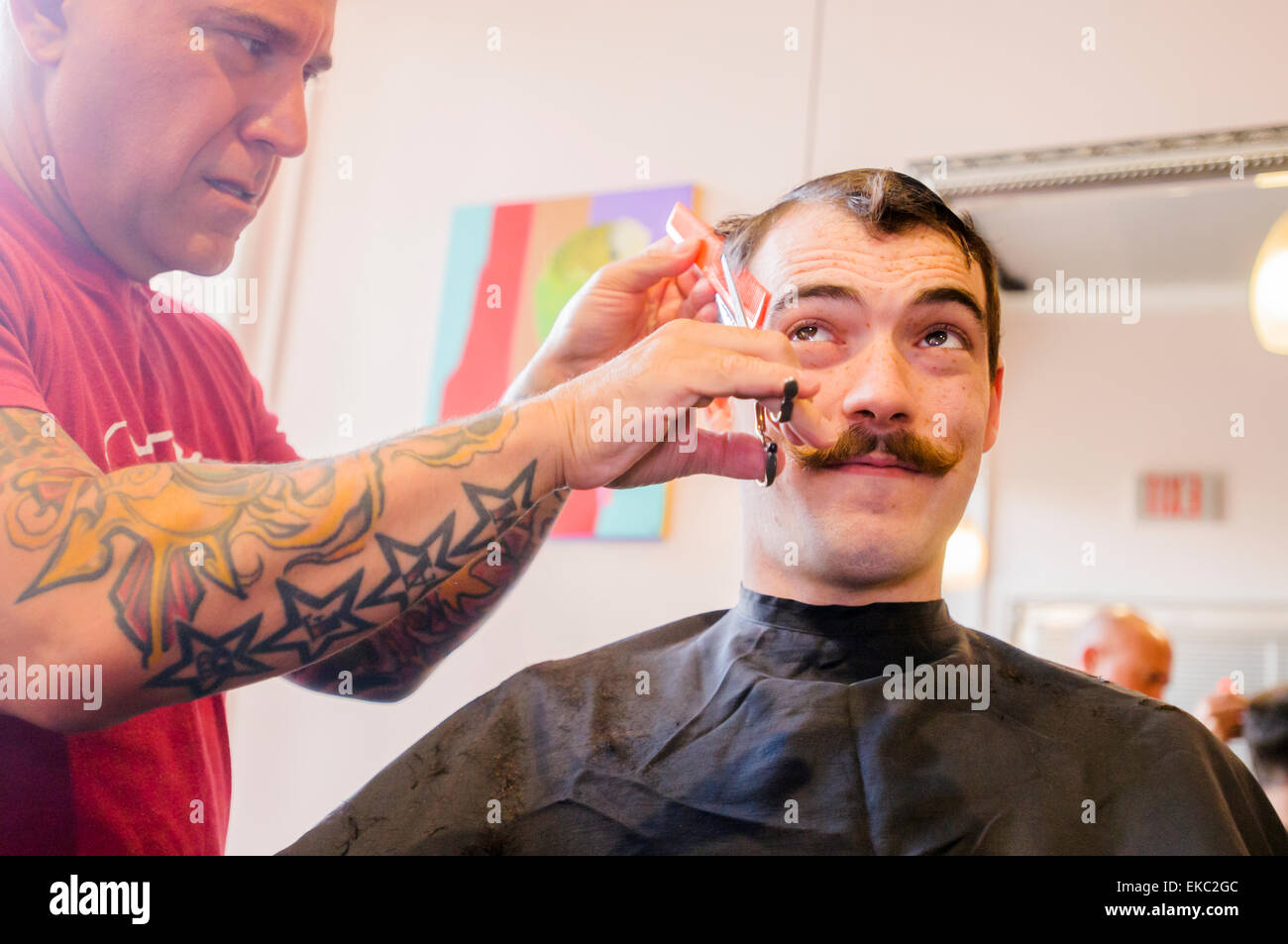 Young man with handlebar moustache having his hair cut - Stock Image