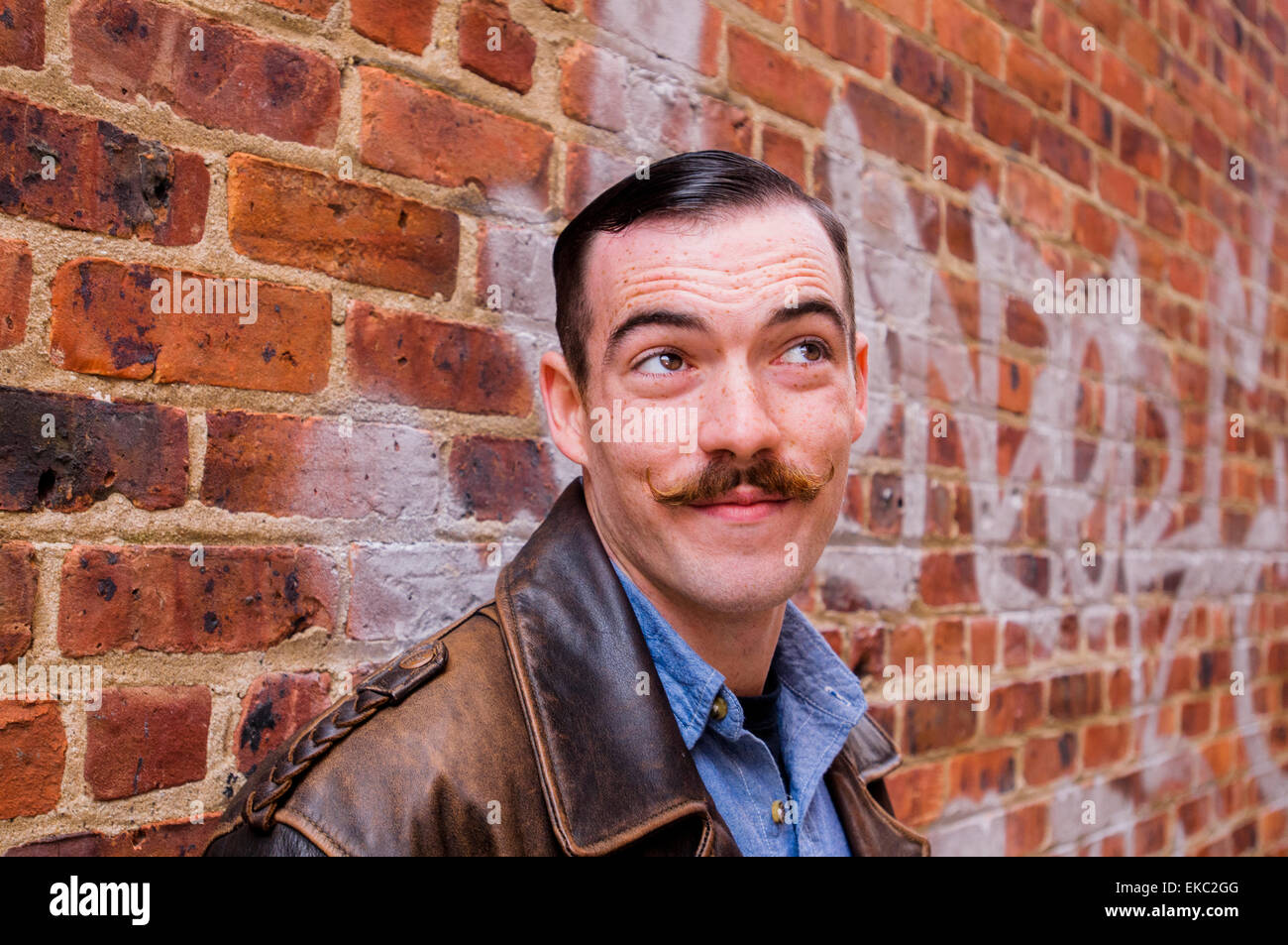 Young man with handlebar moustache, portrait - Stock Image