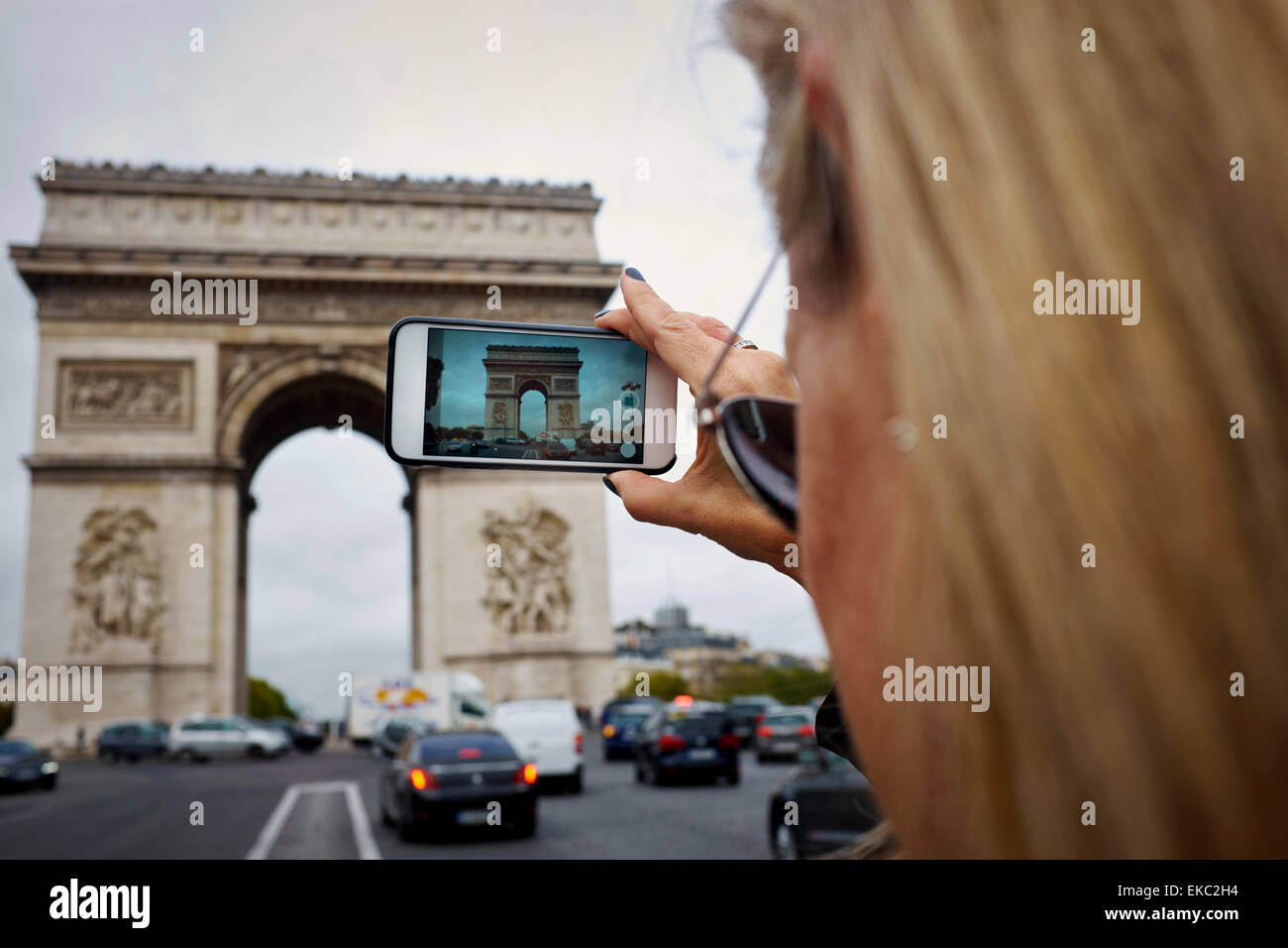 Woman taking photo of the Arc de Triomphe on phone, Paris, France - Stock Image