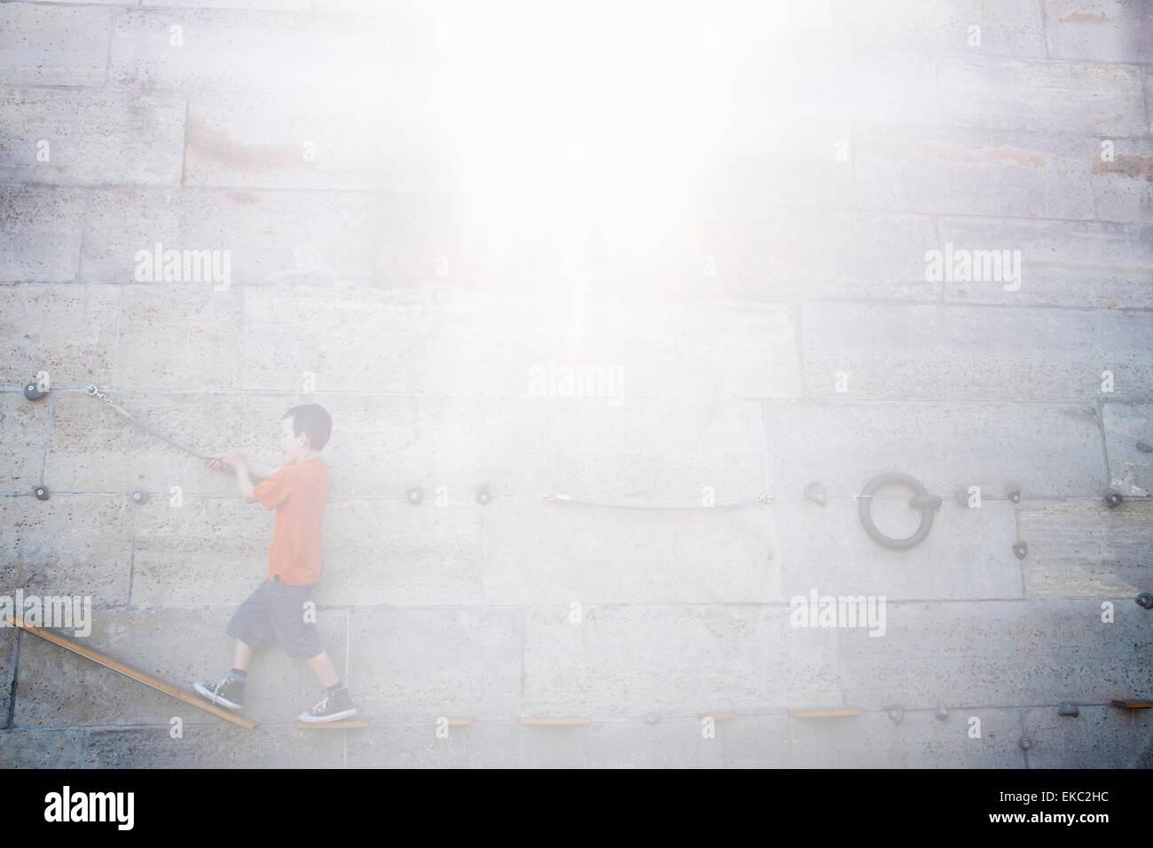Boy climbing along wall - Stock Image
