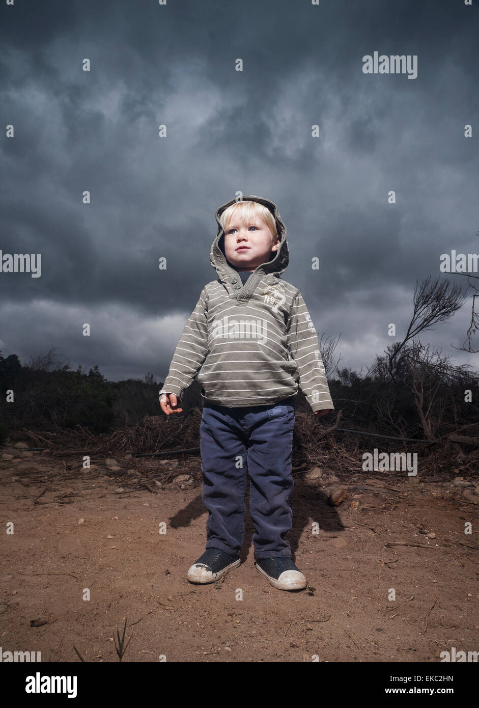 Young boy standing against stormy sky - Stock Image