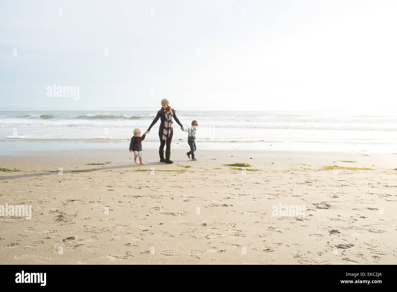 Mother and two sons holding hands on beach - Stock Image
