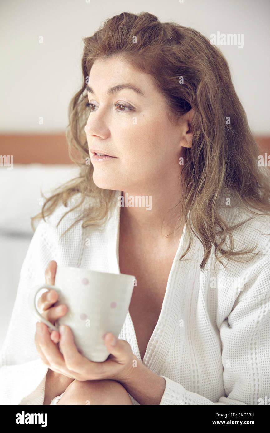 Portrait of mature woman holding mug - Stock Image