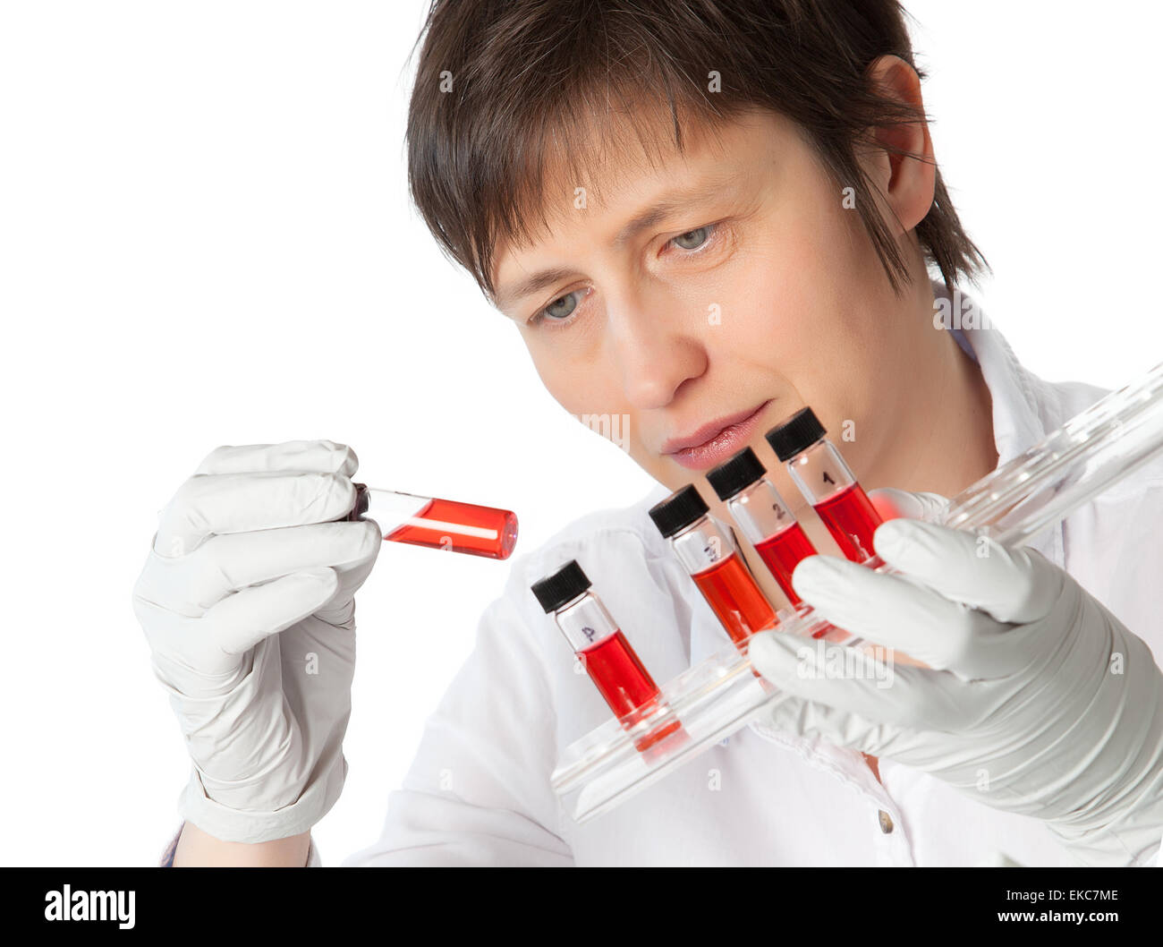 Isolated scientist woman in lab coat with  liquid samples. - Stock Image