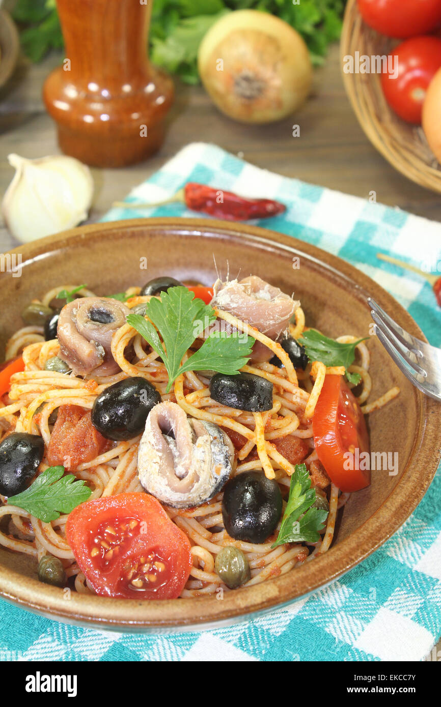 Spaghetti alla puttanesca with olives and anchovies on a napkin Stock Photo