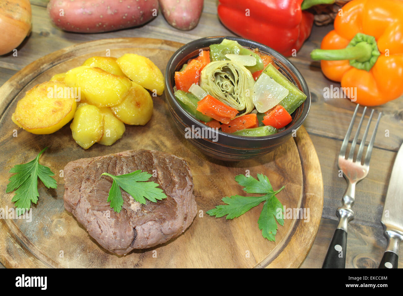 Ostrich steaks with baked potatoes and vegetables on a wooden board Stock Photo