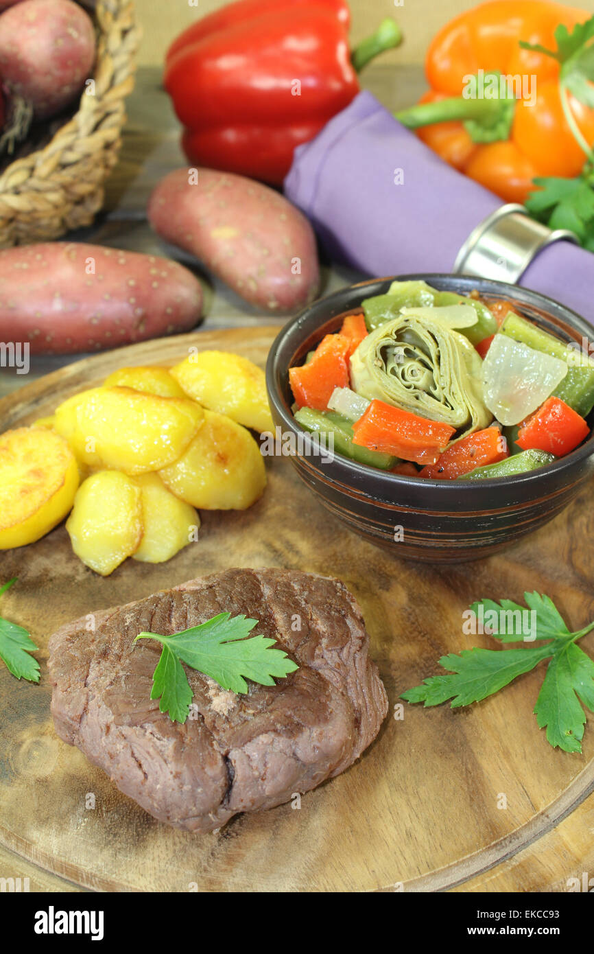 roasted ostrich steak with baked potatoes on a wooden board Stock Photo