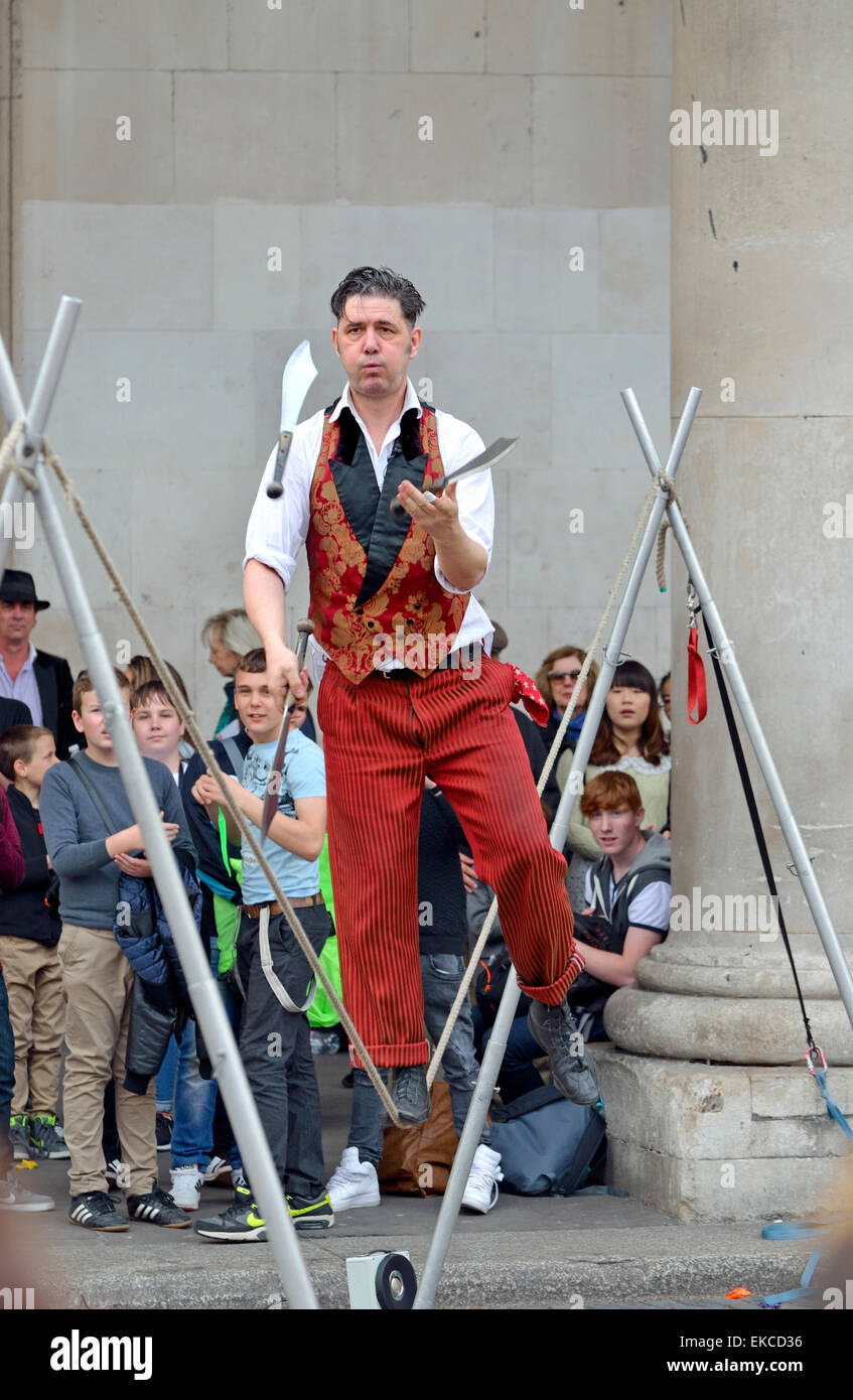 London, England, UK. Street performer in Covent Garden, juggling knives while rope-walking - Stock Image